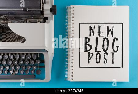 text NEW BLOG POST written on spiral notepad on colorful desk with old typewriter, content creation and blogging concept - Stock Photo