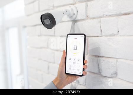 Controlling video surveillance and home alarm with mobile application, close-up on a smart phone with launched app. Concept of a wireless home security systems - Stock Photo