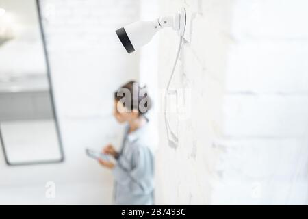 Woman controls home video surveillance with a smartphone indoors, view from the above and ip camera on the foreground. Concept of a wireless home security systems - Stock Photo