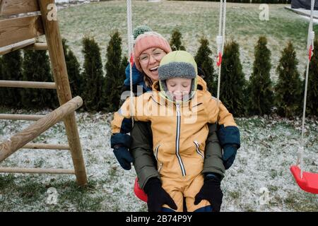 mother and son playing outside laughing whilst on a swing set