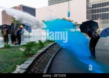 Police use water cannon to disperse protesters at Admiralty. Protesters clash with Anti-riot police during an unauthorised global anti-totalitarian march in Hong Kong, China. - Stock Photo