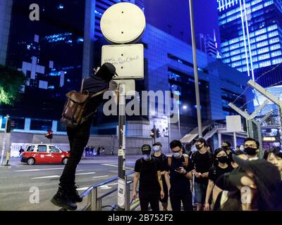 A protester write 'Hong Kong is not China' on a pole. Protesters confront with the police at the 5th anniversary of umbrella movement in Admiralty. Police use water cannon to disperse them. - Stock Photo