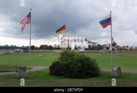 An American, Russian and German flag will fly on 06.09.2017 at the memorial 'The Spirit of the Elbe' in Torgau. The memorial on the banks of the Elbe River commemorates the encounter between Allies and Soviet forces in World War II. On 25 April 1945, the 'handshake of Torgau' with American and Russian soldiers took place here. Hartenfels Castle in the background. [automated translation] - Stock Photo
