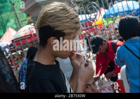 26.01.2017, Yangon, Yangon Region, Republic of the Union of Myanmar, Asia - A young man lights a cigarette in Maha Bandula Park [automated translation] - Stock Photo