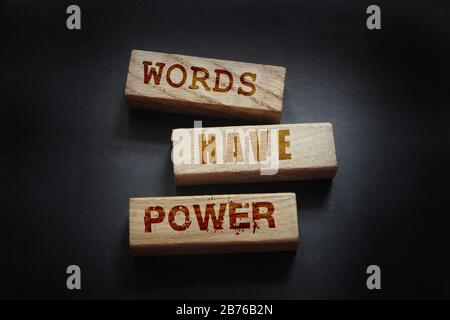 The phrase Words Have Power on wooden blockslaying on black background. Copywriting advertising piar concept - Stock Photo