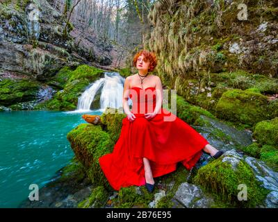Fanciful woman wearing long Red dress legs heels in nature sitting spreading spread legs apart near flowing water waterfall Green forest - Stock Photo