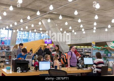 Patrons rush to check out books at the Seattle Central Library in anticipation of an imminent month-long closure on Friday, March 13, 2020. In accordance with public health guidance, the Seattle Public Library will close all locations at 6 p.m. on March 13 to curb the spread of COVID-19 virus. - Stock Photo