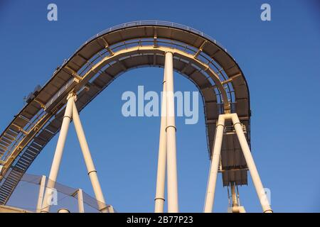 detail of curved rollercoaster track at sunset - Stock Photo