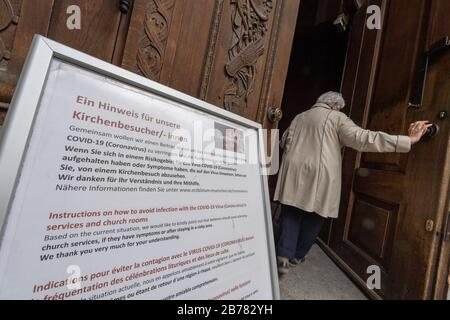 Munich, Germany. 14th Mar, 2020. A woman walks through the entrance door of the Frauenkirche, in front of which an operator advises visitors not to go to church because of the coronavirus. Credit: Peter Kneffel/dpa/Alamy Live News
