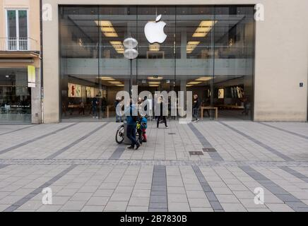 Munich, Germany. 14th Mar, 2020. Some passers-by stand in front of the entrance door of an Applestore in the city centre. Apple closes all stores outside China for two weeks. Credit: Peter Kneffel/dpa/Alamy Live News
