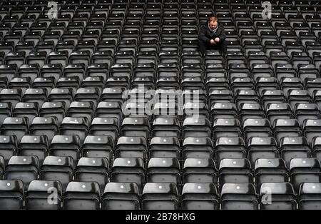 A general view of a fan surrounded by empty seats ahead of the Vanarama National League match at Meadow Lane, Nottingham. - Stock Photo