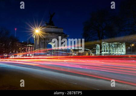 Wellington Arch and Apsley House, Hyde Park Corner, London, England, UK at rush hour with traffic light trails - Stock Photo