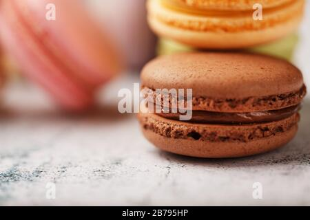 French macaroni cookies of different colors are on the gray table. Still life of confectionery. - Stock Photo