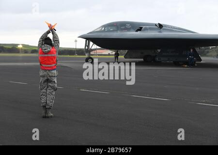 U.S. Air Force Airman 1st Class Noah Rugg, a crew chief assigned to the 131st Bomb Wing, begins to marshal a B-2 Spirit stealth strategic bomber for departure at Lajes Field March 12, 2020 in the Azores, Portugal. - Stock Photo