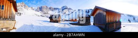 Fuciade San Pellegrino village wooden houses in winter time in dolomites in Italy in snowy day panorama landscape - Stock Photo