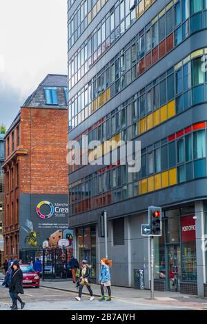 Manchester, United Kingdom - March 1, 2020: People walk past traffic lights in Ancoats area of Manchester - Stock Photo