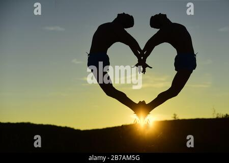 Double silhouette of dancer making heart shape on sunset background. Sports art concept. Athletes train dancing position in air catching sun on tip toes. Men with sportive figures jump and lean back - Stock Photo