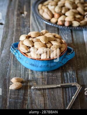 Almonds in a blue bowl on wooden table. Nut cracker tool. Health benefits, nutrition concept. - Stock Photo
