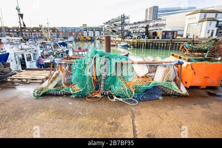 Fishing nets and tackle stored quayside at Camber Quay (The Camber), the ancient port in Old Portsmouth, Hampshire, south coast England - Stock Photo