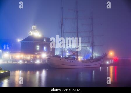 Harlingen, Netherlands - January 09, 2020. Port of Harlingen in fog at night - Stock Photo