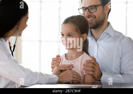 Medical worker listening lungs heartbeat of little girl patient. - Stock Photo
