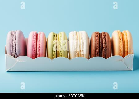 Macaroni cookies of different colors in a white box on a blue background. - Stock Photo