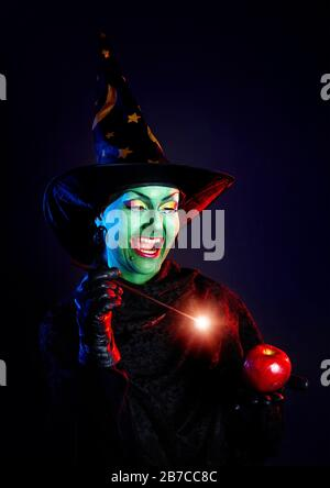 Witch with green skin holding glowing wand and conjure red apple at Halloween on dark background - Stock Photo