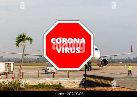 Stop sign with Coronavirus overlaying photo of airplane taxiing on the runway, Siem Reap, Cambodia - Stock Photo