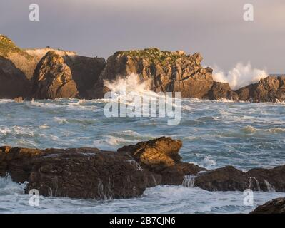 Cormoran rock and splashing waves at sunrise, coast of the Atlantic Ocean/Cantabrian Sea, Punta del Castillo in the Natural Park of Oyambre - Stock Photo