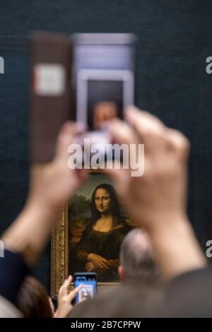 Tourists using their smartphones to take pictures of the Mona Lisa painting by artist Leonardo da Vinci, Louvre Museum, Paris, France, Europe - Stock Photo
