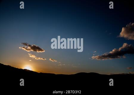 Sunset behind the mountains with clouds, blue sky and sun rays - Stock Photo