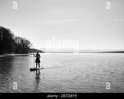 Starnberg, Bavaria, Germany. 15th Mar, 2020. A stand-up paddler on Lake Starnberg near Munich, Germany practices social distancing and flatten the curve during the European Coronavirus outbreak and subsequent measures taken to control the spread. Credit: Sachelle Babbar/ZUMA Wire/Alamy Live News