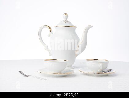 White and gold vintage teapot filled with fresh flowers with a touch of texture in the white tablecloth makes a background with room for text - Stock Photo