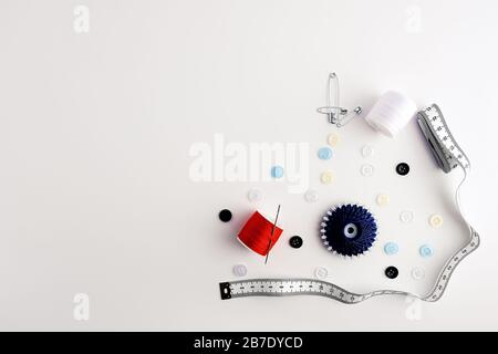 measuring tape, yarns, needles, safety pins, buttons, arranged on white background