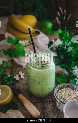 Fresh green smoothie on a rustic background - Stock Photo
