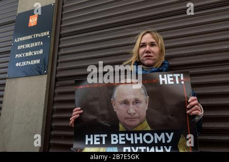 Moscow, Russia. 15th of March, 2020 A woman holds a banner with a message reading 'No to the eternal Putin' during a single protest against the proposed constitutional amendments near the building of the Presidential Executive Office at Staraya Ploshchad Street in central Moscow. On 11 March 2020, Russia's State Duma backed a batch of proposed amendments to the Russian constitution. One of the amendments would make it possible for presidents of Russia to be re-elected regardless of the existing constitutional rule which limits the number of consecutive presidential terms - Stock Photo