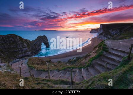 Durdle Door, Lulworth, Dorset, UK.  15th March 2020.  UK Weather.  A spectacular fiery sunset at Durdle Door on the Dorset Jurassic Coast near Lulworth as the cloud clears as high pressure builds in from the South West.  Picture Credit: Graham Hunt/Alamy Live News