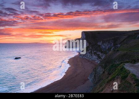 Durdle Door, Lulworth, Dorset, UK.  15th March 2020.  UK Weather.  A spectacular fiery sunset at Durdle Door on the Dorset Jurassic Coast near Lulworth looking towards Swyre Head and Bats Head as the cloud clears as high pressure builds in from the South West.  Picture Credit: Graham Hunt/Alamy Live News