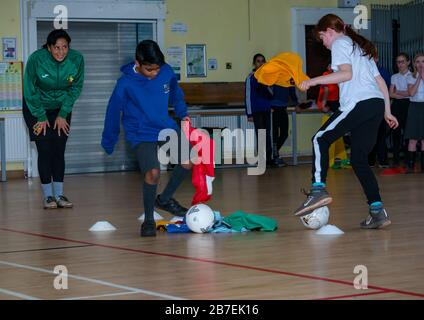School children in sport game with Laura Brooks form Tackle Africa, Davidsons Mains primary school, Edinburgh, Scotland, UK