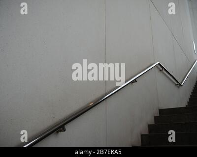 Long shot of silver metal hand railing on a wall beside the stairs in black and white - Stock Photo