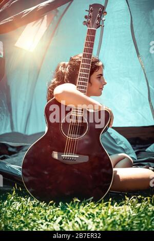 Teen girl with pleasure spending holidays in summer camp, pretty child sitting with a guitar near the tent, singing song and having fun - Stock Photo