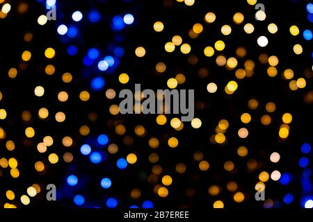 Blue, yellow and orange bokeh circles from New Year Christmas tree lights illuminations with defocused blurred view at night - Stock Photo