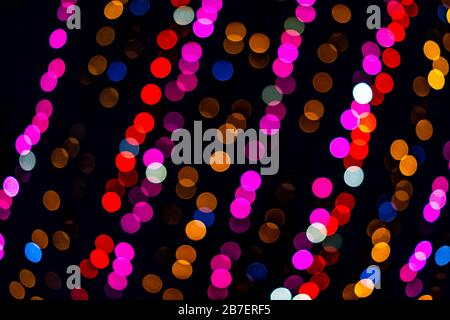 Colorful multicolored red, purple yellow and blue bokeh circles from New Year Christmas tree lights illuminations with defocused blurred view at night - Stock Photo