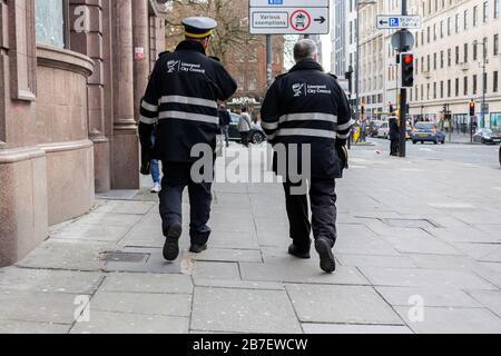 Traffic wardens walking down Lime street, Liverpool - Stock Photo