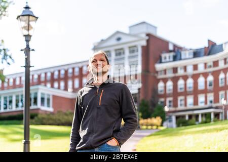 Hot Springs, VA historic homestead brick architecture hotel in downtown town village city in Virginia countryside and tourist man standing happy - Stock Photo