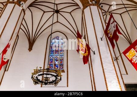 Warsaw, Poland - December 22, 2019: Inside indoors of Roman Catholic church of St. John's Archcathedral with vaulted ceilings, flags chandelier hangin - Stock Photo