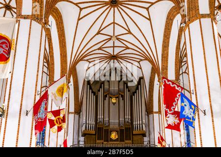 Warsaw, Poland - December 22, 2019: Inside of Roman Catholic church of St. John's Archcathedral with vaulted ceilings, flags and organ pipe musical in - Stock Photo