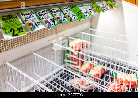 Reston, USA - March 13, 2020: Sold out empty refrigerator freezer shelf racks with frozen fruit grocery food and price tags at Trader Joe's store peop - Stock Photo