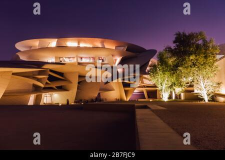 Night time shot of the National Museum of Qatar, with its striking disc-based design, in Doha, Qatar