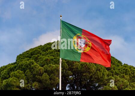 Portuguese flag waving in the wind in Lisbon, Portugal - Stock Photo